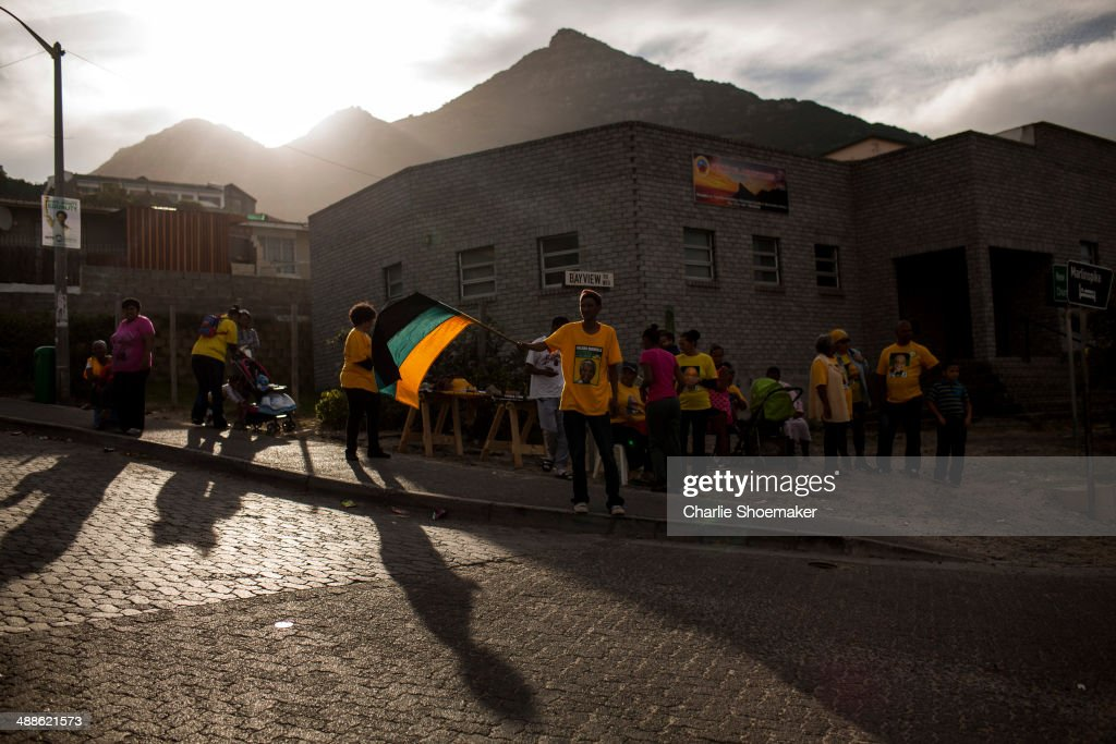 ANC supporters celebrate outside of the Hangberg Sports and Recreation Centre voting station in the Hangberg community in Hout Bay on May 7, 2014 in Cape Town, South Africa. Polls have opened in South Africa's fifth general election since the end of apartheid over 20 years ago. President Jacob Zuma is expected to return to power with the ANC party however his election campaign has been marred by allegations of corruption and he is expected to lose some ground to other parties.