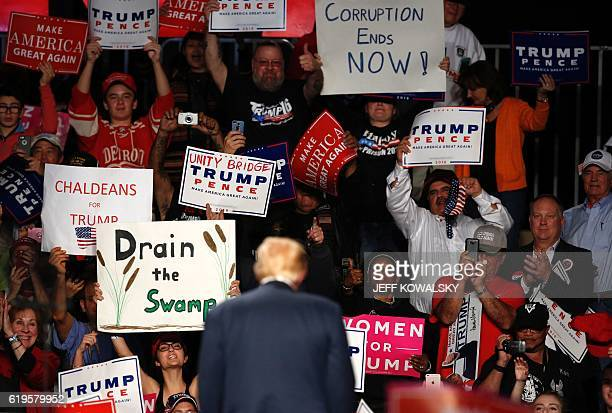 Supporters cheer after US Republican presidential candidate Donald Trump addressed a rally at Macomb Community College on October 31, 2016 in Warren,...