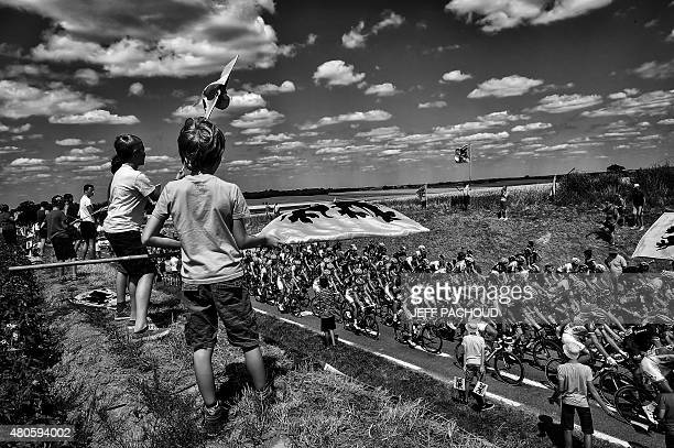 Supporters cheer along the road as the pack rides during the 1595 km third stage of the 102nd edition of the Tour de France cycling race on July 6...