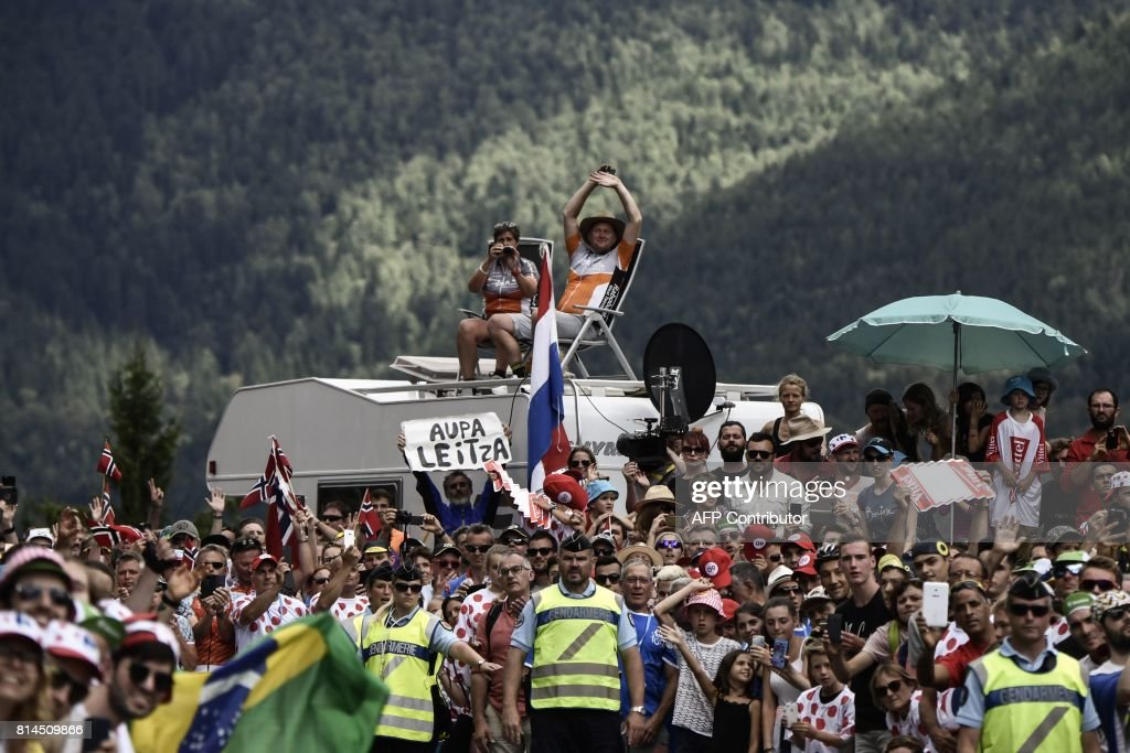 Supporters cheer along the road during the 101 km thirteenth stage of the 104th edition of the Tour de France cycling race on July 14, 2017 between Saint-Girons and Foix. / AFP PHOTO / Jeff PACHOUD