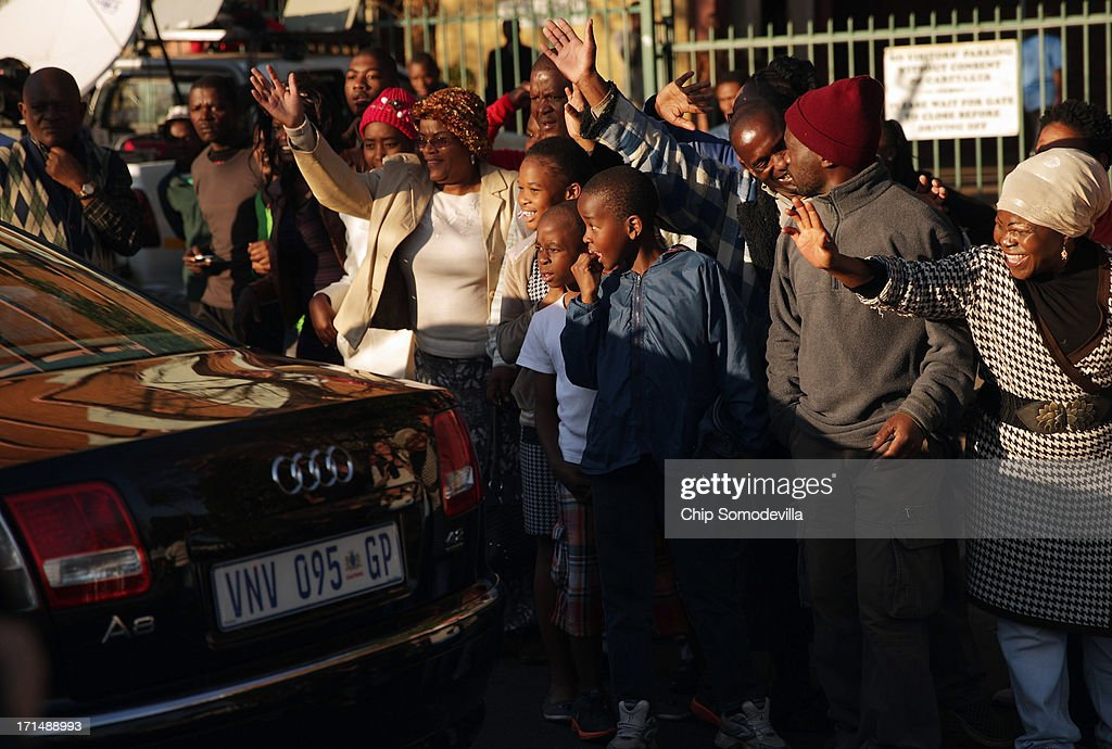 Supporters cheer and wave as Winnie Madikizela-Mandela's car leaves the Mediclinic Heart Hospital where her ex-husband former South African President Nelson Mandela is being treated June 25, 2013 in Pretoria, South Africa. South African President Jacob Zuma confirmed on June 23 that Mandela's condition has become critical since he was admitted to the hospital over two weeks ago for a recurring lung infection.