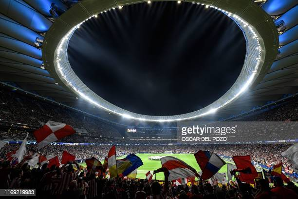 Supporters cheer and wave flags from the stands prior to the UEFA Champions League Group D football match between Atletico Madrid and Juventus, at...