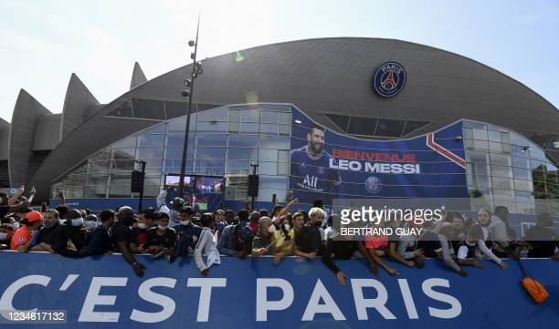 Supporters cheer as Argentinian football player Lionel Messi attends his unveiling press conference at the French football club Paris Saint-Germain's...
