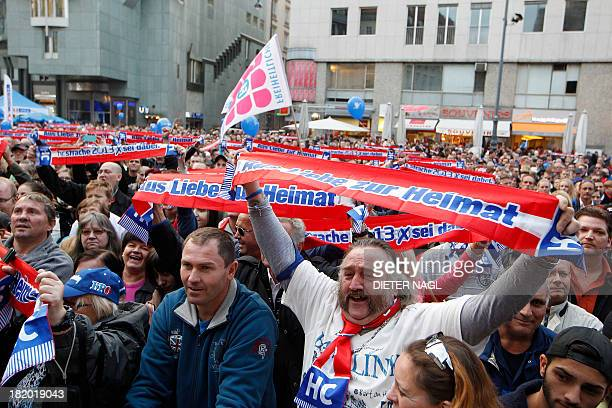 Supporters cheer as Austrian Freedom party head and main candidate HeinzChristian Strache speaks during a rally on September 27 2013 ahead of next...