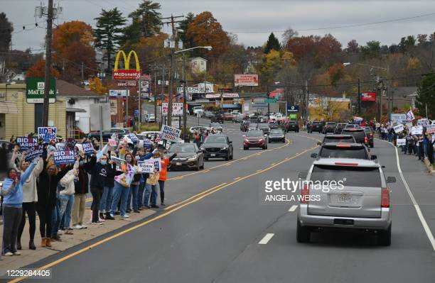Supporters cheer as Democratic presidential nominee and former Vice President Joe Biden's motorcade drives by on the way to a Drive-In event with Bon...