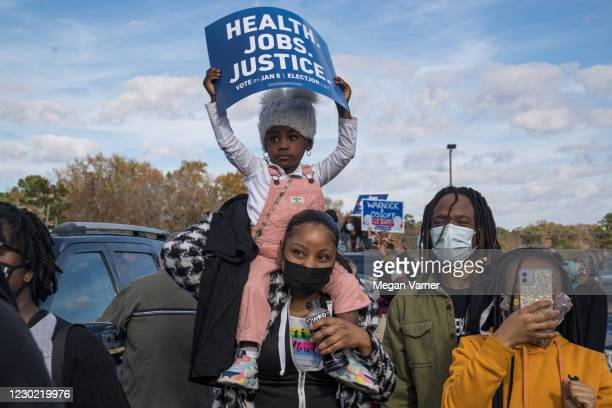Supporters cheer as Democratic U.S. Senate candidates Jon Ossoff and Rev. Raphael Warnock speak at a Its Time to Vote Rally on December 19, 2020 in...