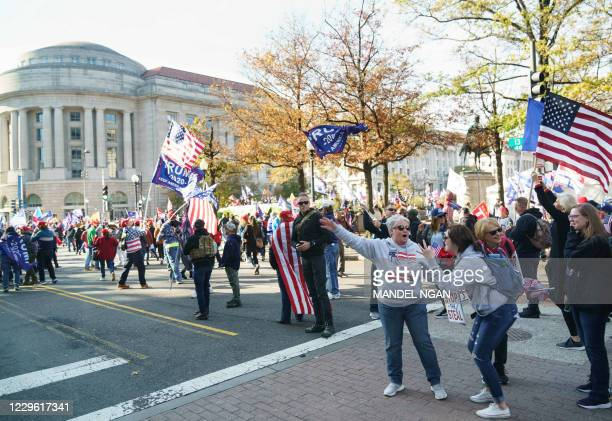 Supporters cheer as the motorcade carrying US President Donald Trump passes by Freedom Plaza in Washington, DC on November 14, 2020. - Supporters are...