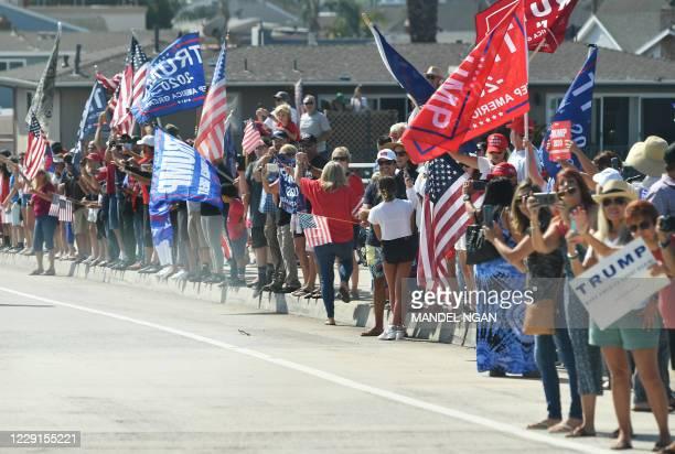 Supporters cheer as the motorcade of US President Donald Trump passes by near John Wayne Airport in Santa Ana, California on October 18, 2020. -...
