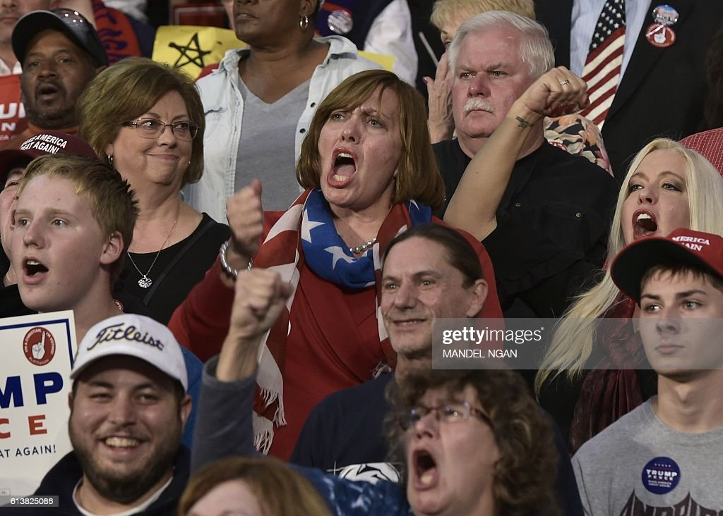 Supporters cheer as they watch as Republican presidential nominee Donald Trump speak during a rally at Ambridge Area Senior High School on October 10, 2016 in Ambridge, Pennsylvania. / AFP / MANDEL