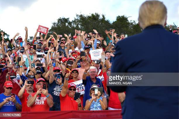 Supporters cheer as US President Donald Trump arrives for a campaign rally at The Villages Polo Club in The Villages, Florida on October 23, 2020.