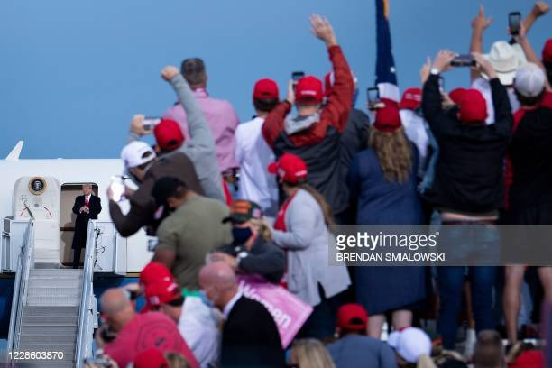 """Supporters cheer as US President Donald Trump arrives for a """"Great American Comeback"""" rally in Fayetteville, North Carolina, on September 19, 2020."""