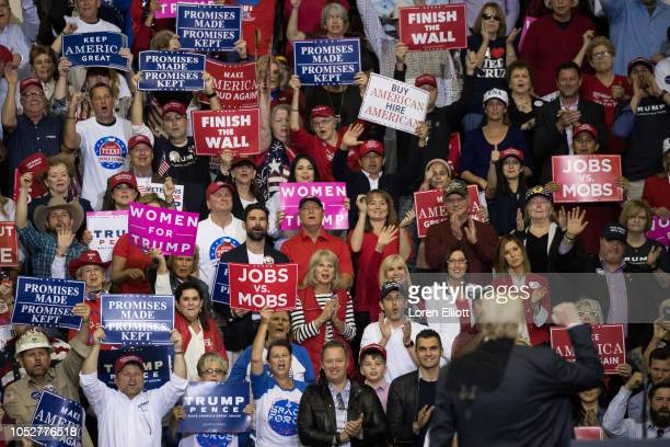 Supporters cheer as US President Donald Trump speaks during a rally in support of Sen Ted Cruz on October 22 2018 at the Toyota Center in Houston...