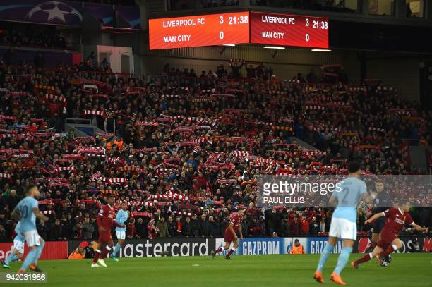 Supporters cheer during the UEFA Champions League first leg quarterfinal football match between Liverpool and Manchester City at Anfield stadium in...