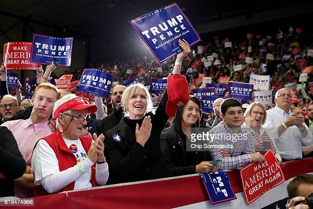 Supporters cheer for Republican presidential nominee Donald Trump as he takes the stage during a campaign rally at the Deltaplex Arena October 31...