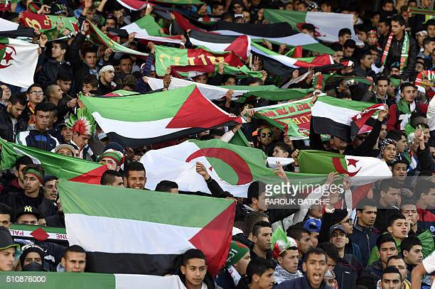 Supporters cheer for their teams during a friendly football match between the Palestinian and Algerian Olympic football teams at the 5 Juillet 1962...
