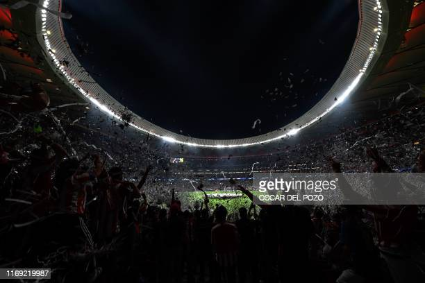 TOPSHOT Supporters cheer from the stands prior to the UEFA Champions League Group D football match between Atletico Madrid and Juventus at The Wanda...