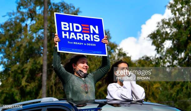 Supporters cheer from their car holding a Biden-Harris placard as people take to the streets in Los Angeles on November 7, 2020 to celebrate Joe...