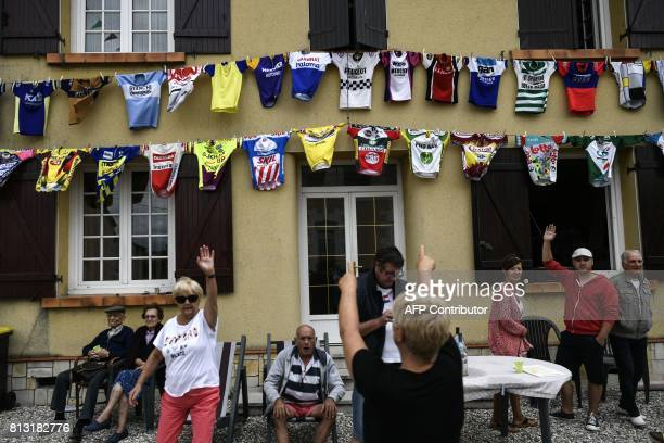 Supporters cheer in front of jerseys set up on the facade of a house along the road during the 2035 km eleventh stage of the 104th edition of the...