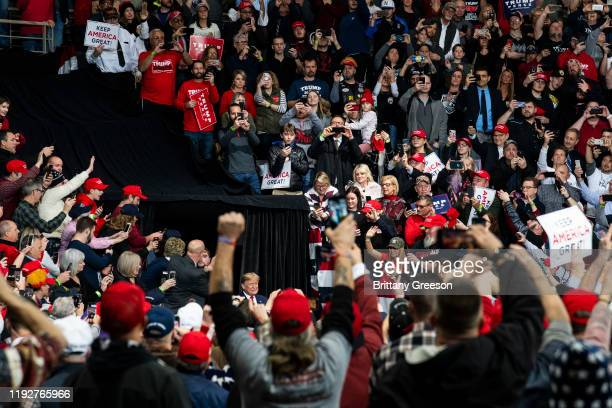 Supporters cheer in the crowd as President Donald Trump makes his entrance at a Keep America Great campaign rally at the Huntington Center on January...