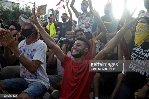 Supporters cheer outside the army-barricaded parliament building in the capital Tunis on July 26 after the president dismissed the prime minister and...