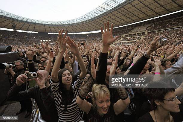 Supporters cheer the British band Depeche Mode during their concert at the Olympic stadium in Berlin on June 10 2009 This concert is part of their...