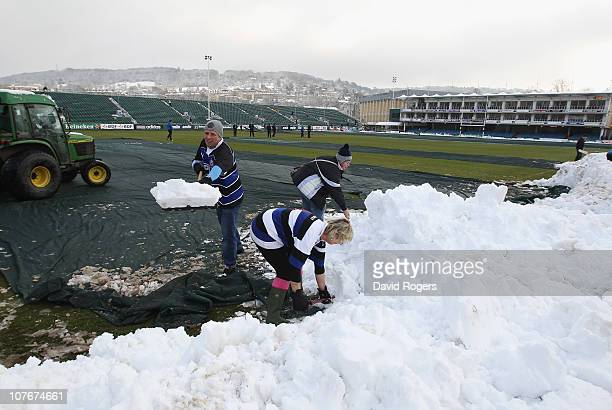 Supporters clear the pitch of snow prior to the Heineken Cup pool 4 match between Bath and Ulster at the Recreation Ground on December 18, 2010 in...