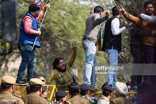 BJP supporters climb on barricades during their protest against the water tariff hike and tried to march towards Delhi Chief Minister Arvind...