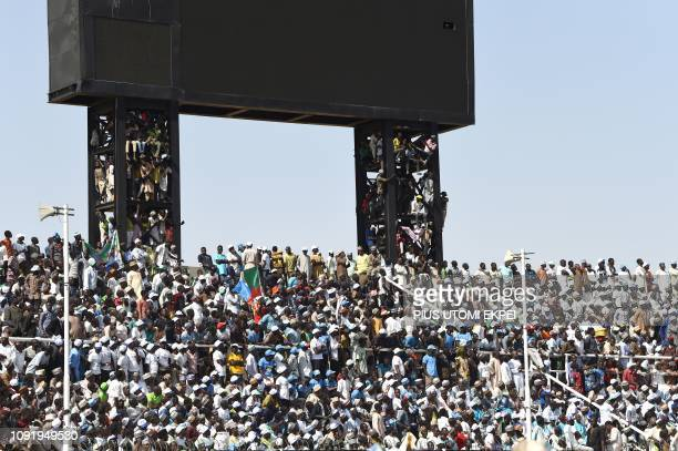 Supporters climb score board to watch candidate of the ruling All Progressives Congress President Mohammadu Buhari during his presidential campaign...