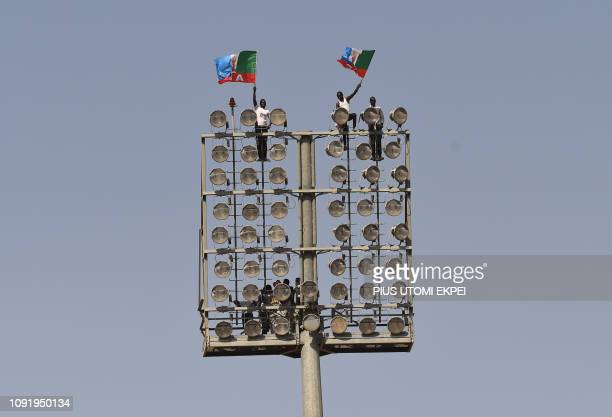 TOPSHOT Supporters climbed on spots wave flags of the ruling All Progressives Congress during incumbent President Mohammadu Buhari's presidential...