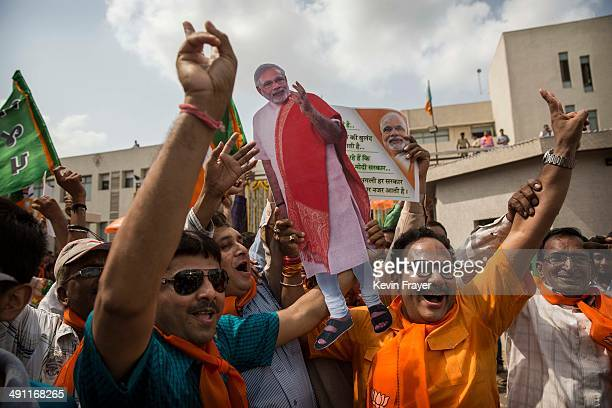 BJP supporters dance as poll results come in at the party's headquarters on May 16 2014 in Ahmedabad India Early indications from the Indian election...