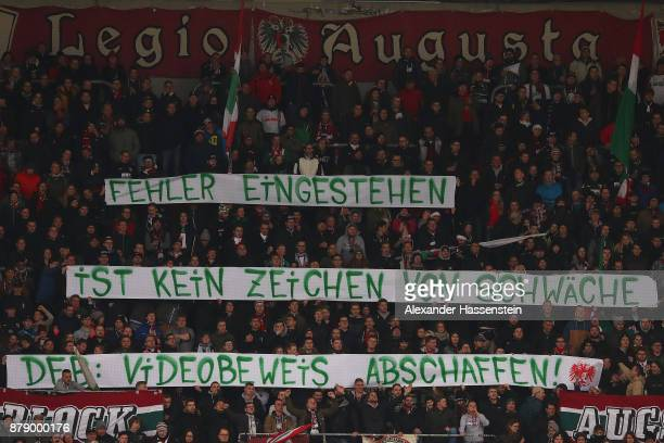 Supporters display a banner against video refereeing during the Bundesliga match between FC Augsburg and VfL Wolfsburg at WWKArena on November 25...