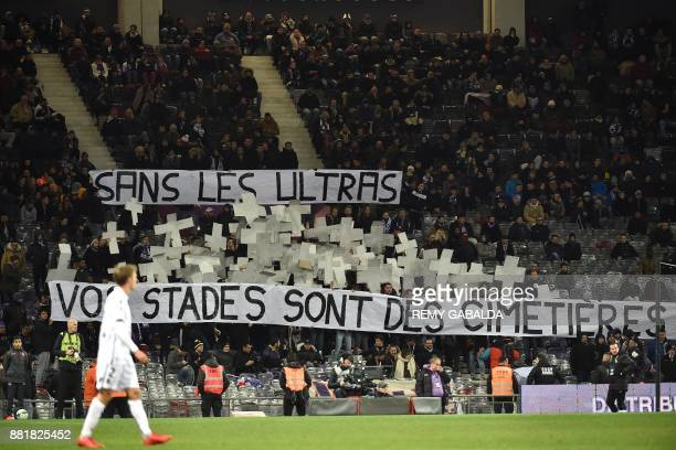 Supporters display a banner reading 'without the 'ultras' fans your stadiums are like cemetaries' during the French L1 football match between...