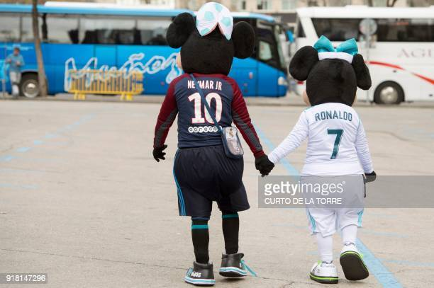 TOPSHOT Supporters dressed as Paris SaintGermain's Brazilian forward Neymar Jr and Real Madrid's Portuguese forward Cristiano Ronaldo walk outside...
