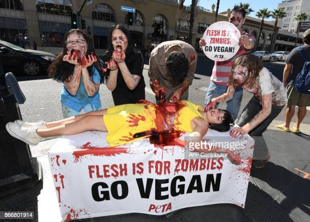 supporters dressed like zombies pretend to gorge themselves on a victim during a Halloween themed protest against consumption of animal meat in...