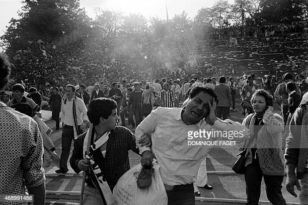 Supporters flee 29 May 1985 the scene of riots in Heysel football stadium in Brussels after thirtynine Juventus football fans died during rioting at...