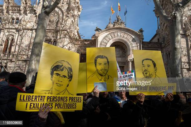 Supporters for the independence of Catalonia hold placards and portraits of the new Catalan MEPs, Puigdemont, Comín and Junqueras during the rally....