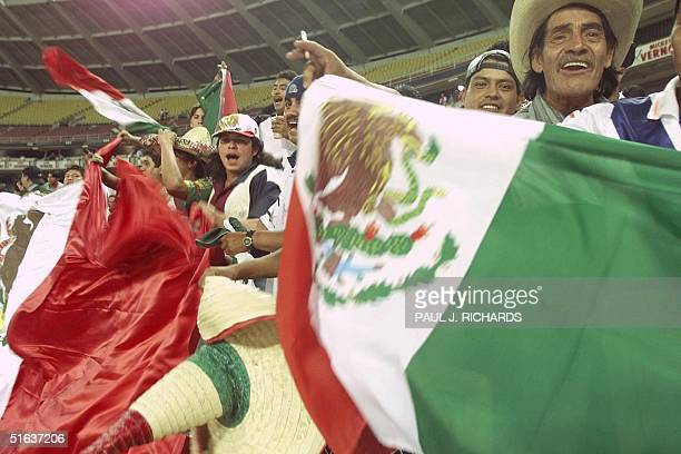 Supporters for two of Mexico's soccer teams CSD Leon and CD Toluca FC wave the Mexican flag to support their teams as they faced DC United and...