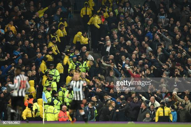 Supporters from rival clubs are kept apart by stewards and police during the English Premier League football match between Manchester City and...