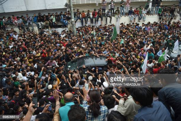 TOPSHOT Supporters gather around the vehicle carrying Pakistan 's cricket captain Sarfaraz Ahmed upon his arrival from London in Karachi on June 20...