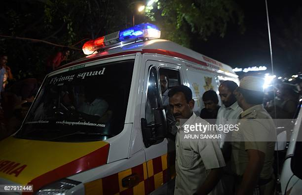 Supporters gather as an ambulance carrying the remains of Tamil Nadu state leader Jayalalithaa Jayaram are to Rajaji hall from the hospital where she...