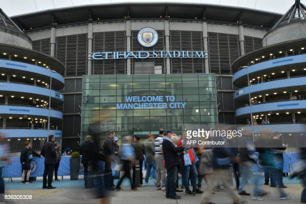 Supporters gather outside the stadium before the English Premier League football match between Manchester City and Everton at the Etihad Stadium in...