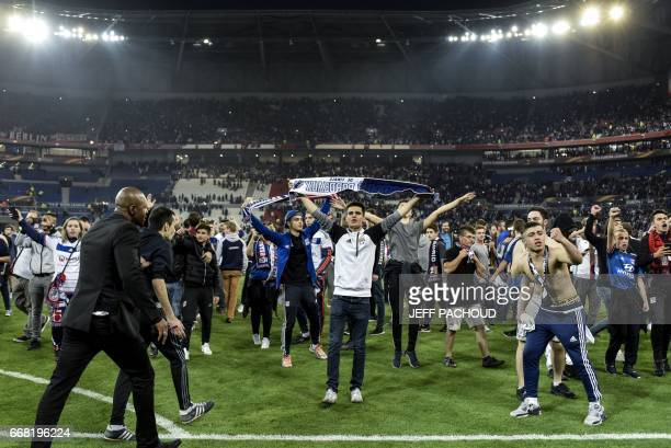 Supporters gesture after entering on the pitch before the UEFA Europa League first leg quarter final football match between Lyon and Besiktas on...