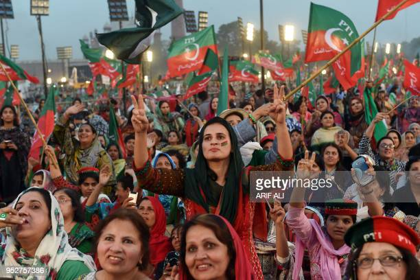 Supporters gesture and wave flags of the Pakistani political party Pakistan TehreekeInsaf as they attend a rally with Pakistan opposition leader and...