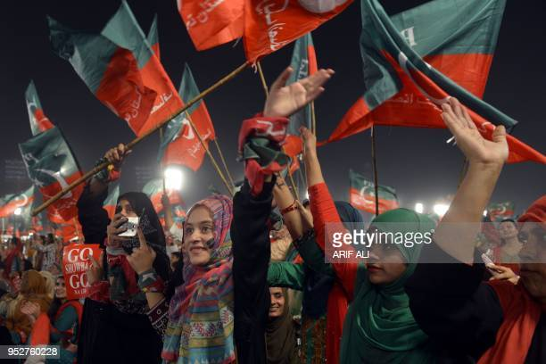 TOPSHOT Supporters gesture and wave flags of the Pakistani political party Pakistan TehreekeInsaf as they attend a rally with Pakistan opposition...