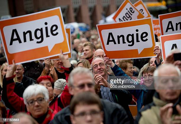 Supporters greet German Chancellor Angela Merkel with posters reading 'Angie' at an election campaign event of her German Christian Democratic Union...
