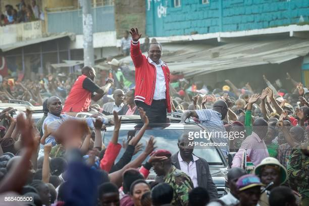 Supporters greet Kenya's President Uhuru Kenyatta as he gestures and acknowledges the audience from a car roof with DeputyPresident William Ruto...