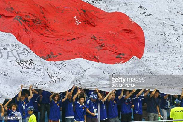 Supporters hoist a giant Japanese flag, spread over the bleechers of Osaka Nagai Stadium, 14 June, 2002 before match 45 group H of the 2002 FIFA...