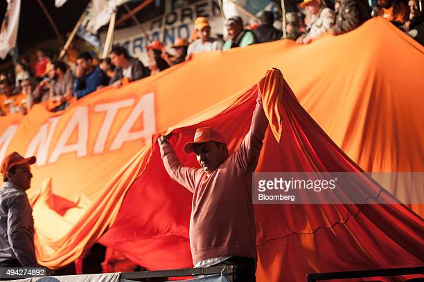 Supporters hold a banner at the campaign headquarters of presidential candidate Daniel Scioli on election night in Buenos Aires Argentina on Sunday...