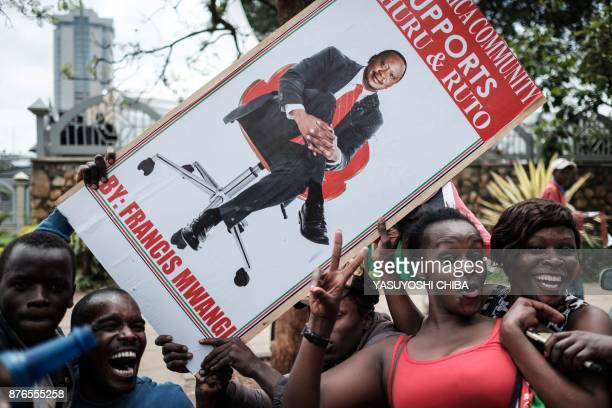 TOPSHOT Supporters hold a banner bearing a picture of President Uhuru Kenyatta as they celebrate on November 20 2017 in Nairobi after Kenya's Supreme...