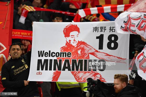 Supporters hold a banner for Liverpool's new signing Japanese midfielder Takumi Minamino during the English Premier League football match between...